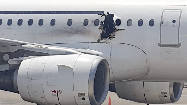 The plane operated by Daallo Airlines sits on the runway in Mogadishu. A gaping hole in the commercial airliner forced ...