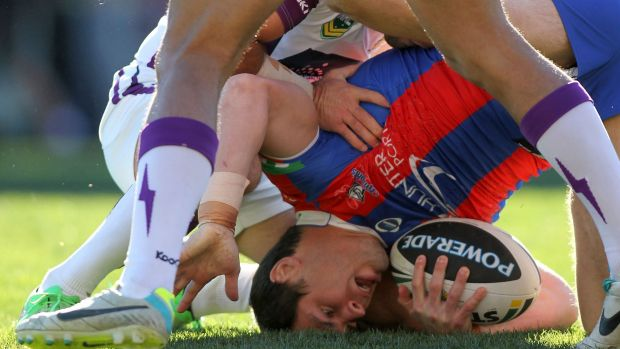 James McManus of the Knights is tackled to the ground in August 2013.