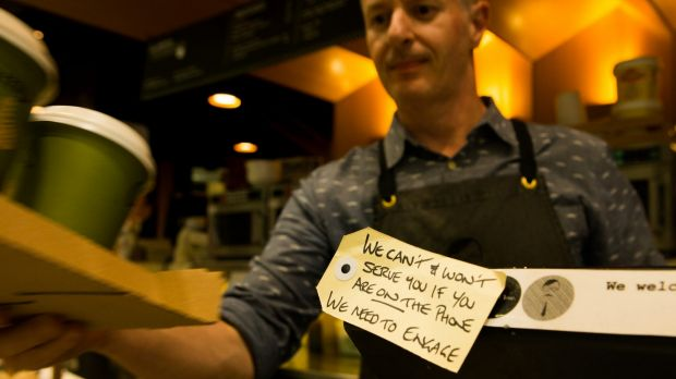 James English put a handwritten note on the cash register to ban mobile phones.