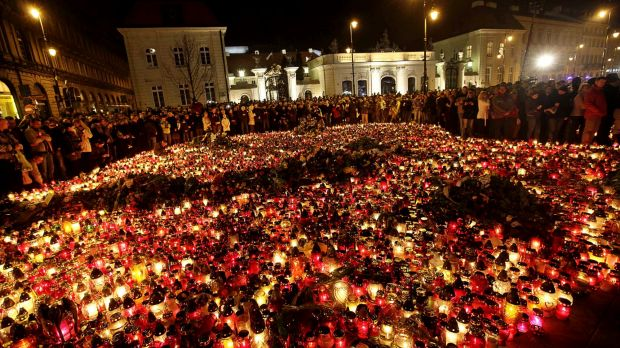 People place candles and lay flowers in front of the Presidential Palace in Warsaw, Poland on April 10, 2010, as news ...
