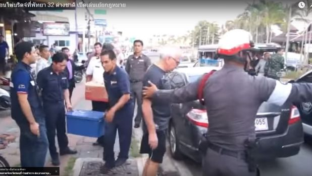 An elderly bridge player is arrested by a Thai policeman in Pattaya.