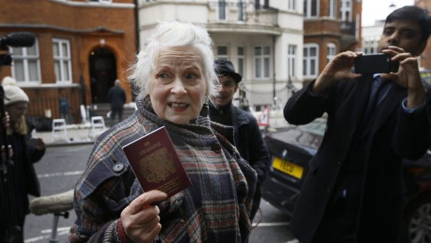 British Fashion designer Vivienne Westwood shows her passport to the media as she arrives outside the Ecuadorean embassy ...