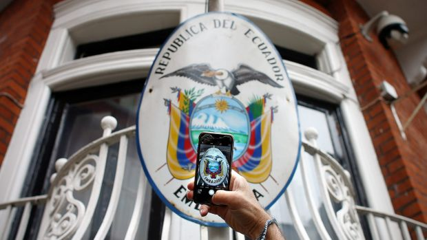 A man photographs the sign on the balcony of the Ecuadorian embassy in London on Thursday.