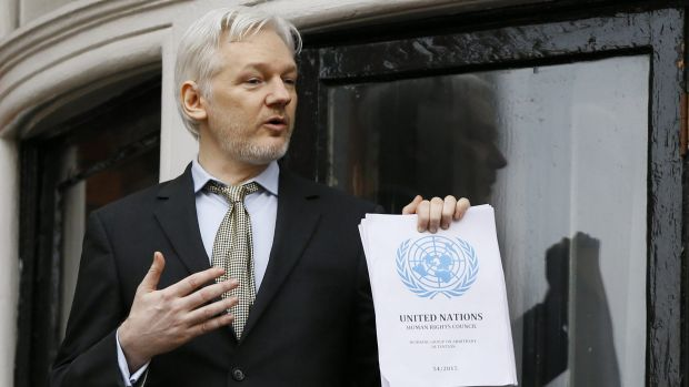 Julian Assange, pictured on the balcony of Ecuador's London embassy, holds the UN report that says he is being ...