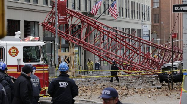 A collapsed crane lies on the street on Friday in New York.
