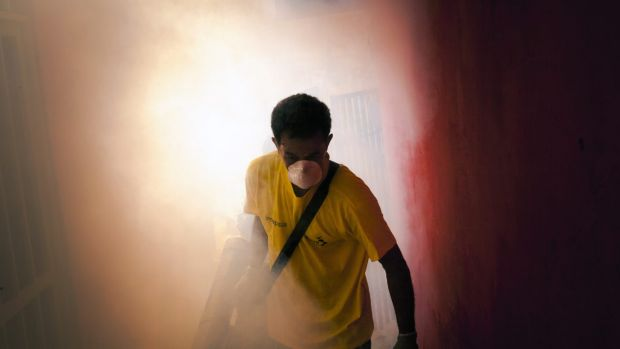 A worker sprays insecticide to eradicate the mosquitoes that carry the Zika virus in the Petare neighbourhood on the ...