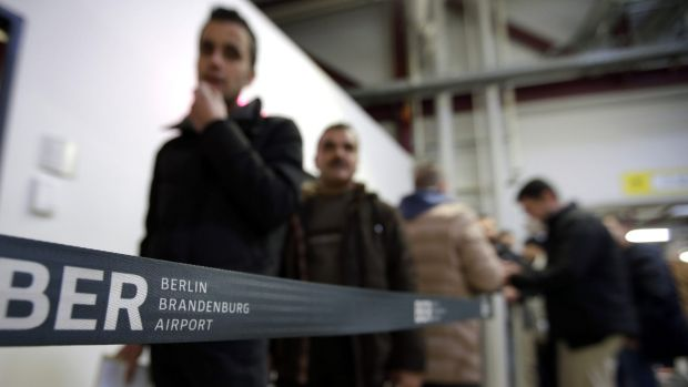 Men leaving Germany queue up in front of a federal police office at the Tegel airport in Berlin.