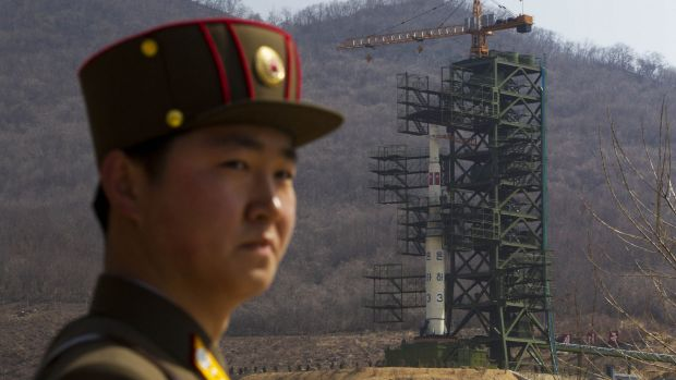 A North Korean soldier stands in front of the Unha 3 rocket at a launching site at Tongchang-ri, in 2012.