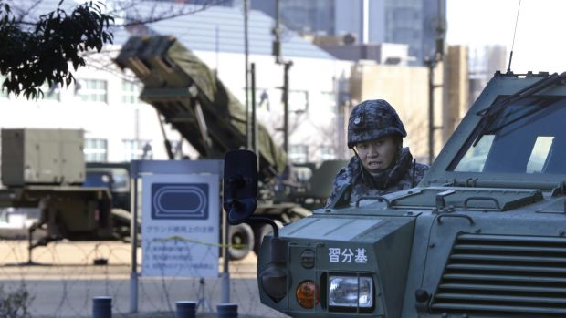A member of the Japan Self-Defence Forces stands near a Patriot missile unit deployed for North Korea's rocket launch in ...