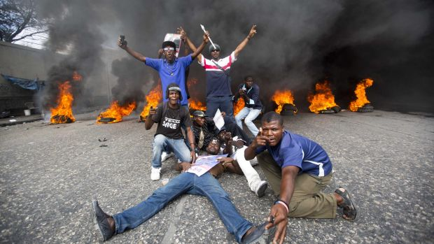 Demonstrators pose in front of a burning barricade during a protest to demand the president's resignation.