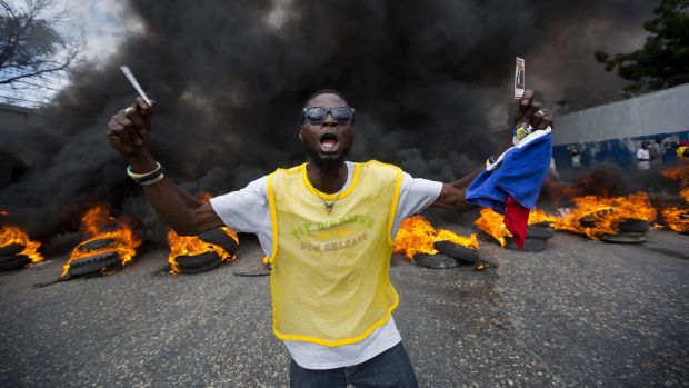 An anti-government demonstrator holds up a picture of former president Jean Bertrand Aristide as he demands the ...