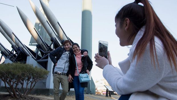 Tourists pose in front of  model missiles, including a North Korean Scud-B, at the War Memorial of Korea in Seoul. North ...