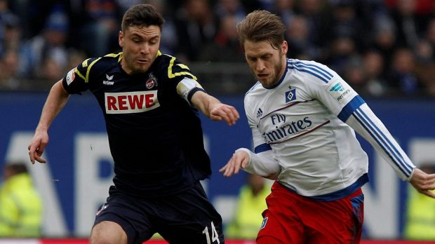 Cologne's Jonas Hector, left, and Hamburg's Aaron Hunt challenge for the ball.