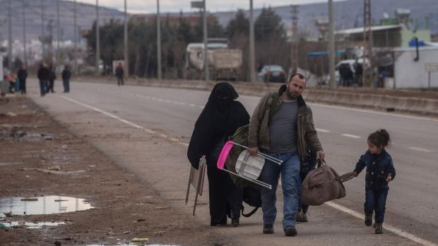 People fleeing air strikes walk to a temporary refugee complex on Sunday.
