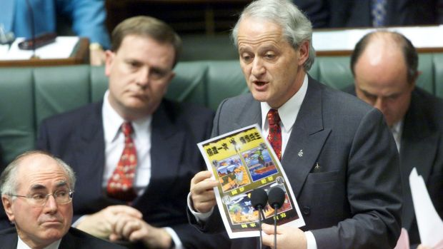 Philip Ruddock  speaks about illegal boat people in Parliament, while  holding a poster on the subject.