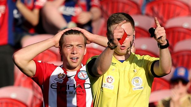 Referee Adam Fielding issues a red card to Jacob Melling of Melbourne City.