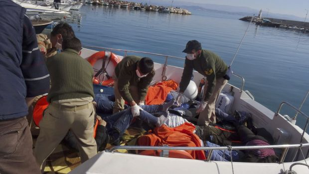 Rescue workers with the bodies of migrants who drowned off the coast of Turkey on Monday.