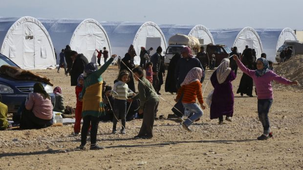 Displaced Syrian children play on Monday at a temporary refugee camp in northern Syria, near Bab al-Salameh border ...