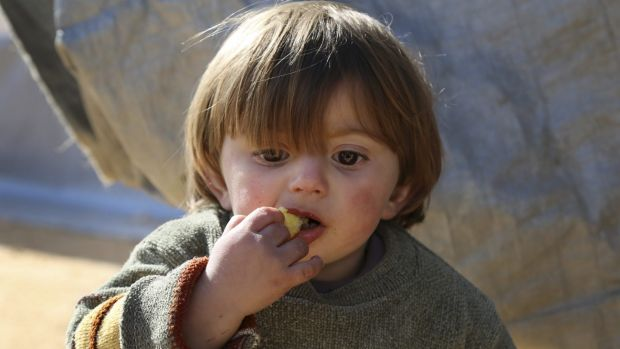 A displaced Syrian boy eats at a temporary refugee camp in northern Syria, near the Bab al-Salameh border crossing with ...