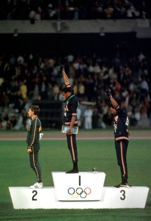 Peter Norman, Tommie Smith  and John Carlos. Smith and Carlos give a Black Power salute on the medal podium at the 1968 ...
