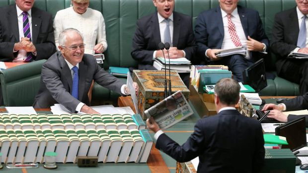 Opposition Leader Bill Shorten wields a newspaper with a report on Medicare changes during question time.
