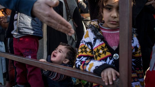 Syrian refugees wait to cross the border into Turkey.