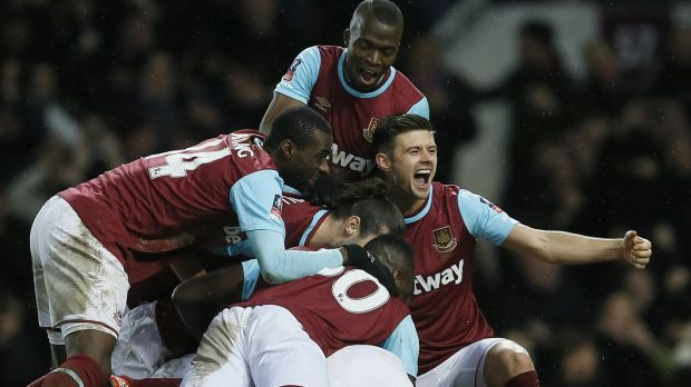 West Ham's Angelo Ogbonna (hidden) is swamped by teammates after scoring the winning goal against Liverpool.