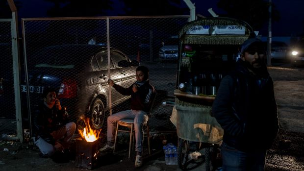 Street vendors keep warm by a fire at the closed Turkish border gate in Kilis on Tuesday.