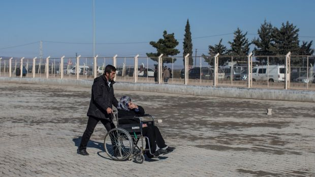 A man pushes a woman in a wheelchair towards the entrance of the Kilis refugee camp at the closed Turkish border gate on ...