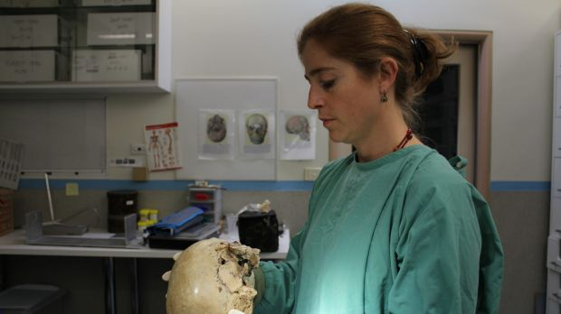 Victorian forensic anthropologist Dr Soren Blau examines a skull in the Victorian Institute of Forensic Medicine mortuary.