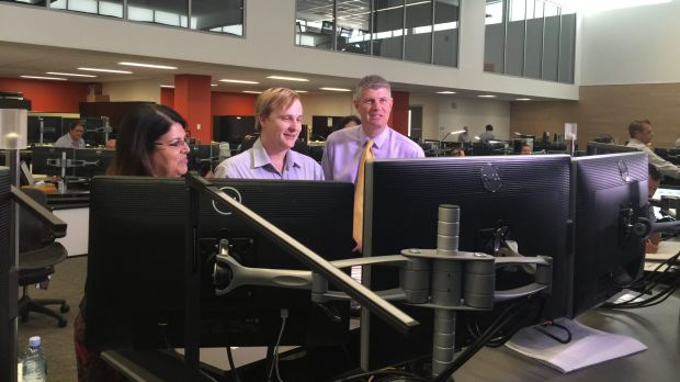 Employment Minister Grace Grace and Transport Minister Stirling Hinchliffe, with a Queensland Rail employee (centre), ...