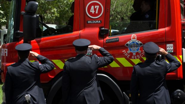 Firefighters salute as a firetruck from Mildura emblazoned with the number 47, drives past.