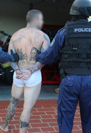 A man is led away by police at Hamlyn Terrace, Wyong.