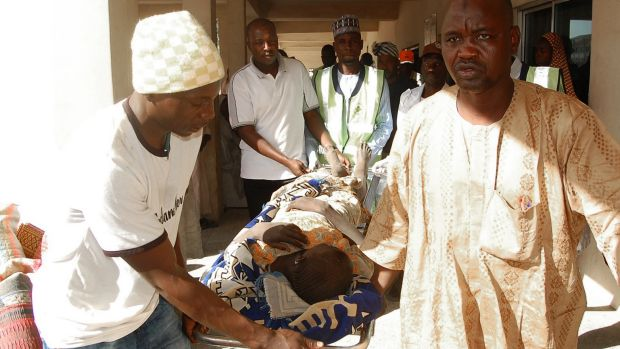 Rescue workers transport a victim of a suicide bomb attack at a refugee for treatment at a hospital in Maiduguri, ...