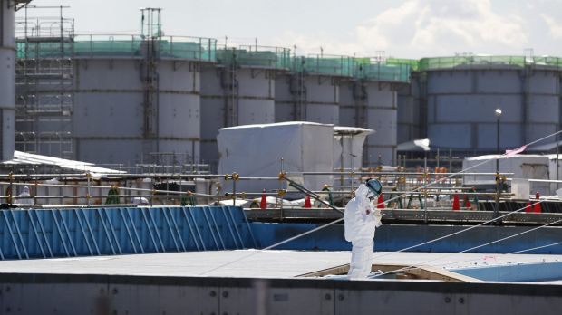 A worker takes notes in front of storage tanks for radioactive water at the power plant on Wednesday.