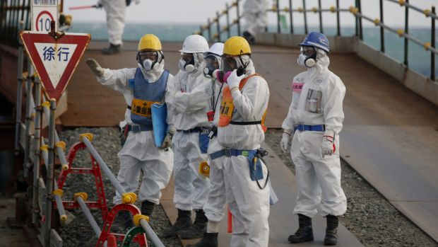 Workers stand near the No. 3 and No. 4 reactor buildings at the Fukushima No. 1 nuclear power plant on Wednesday.
