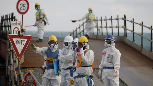Workers stand near the No. 3 and No. 4 reactor buildings at Tokyo Electric Power Co's tsunami-crippled Fukushima ...