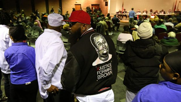 Mike Brown snr, centre, listens to the Ferguson city council meeting, where the negotiations with the Justice Department ...