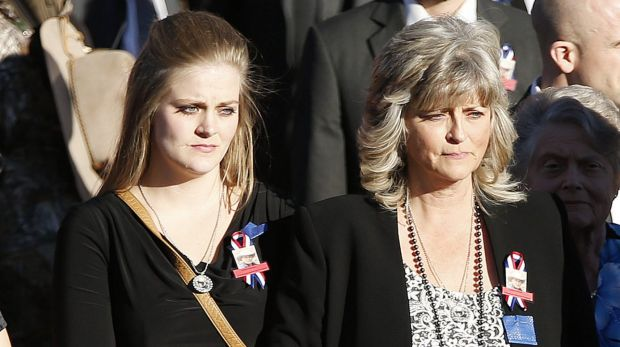 LaVoy Finicum's wife Jeanette and daughter Brittney Beck watch as his casket is carried from the church.
