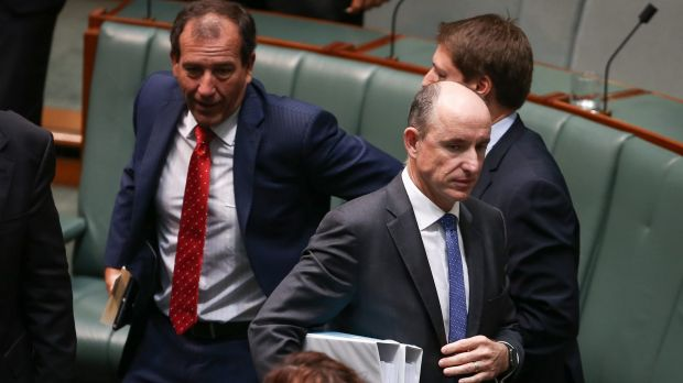 Stuart Robert, Minister for Human Services and Veterans Affairs, walks past colleague Mal Brough on Thursday.