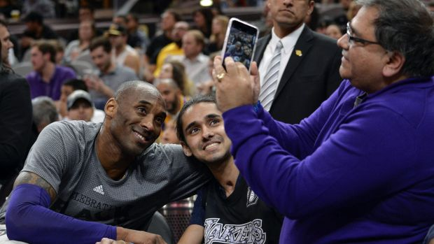 Los Angeles Lakers guard Kobe Bryant poses for a photo with a fan.
