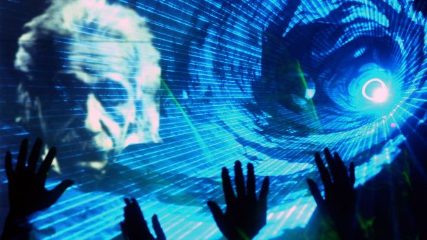Chinese physicists wave as an image of Albert Einstein is projected during a laser show at a telecommunications company ...