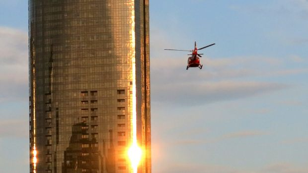 A helicopter flies through Melbourne skyscrapers along the Yarra River.