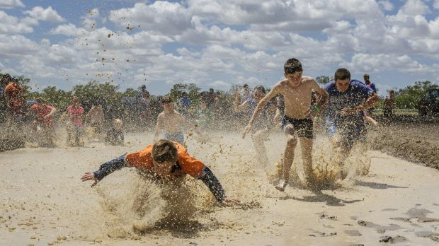 Kids enjoying a race through a mud hole. For many kids in Walgett, recent rains were the first they have experienced.