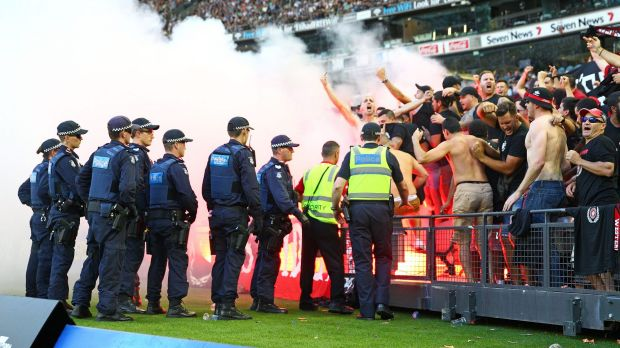 Smoke alarm: Wanderers fans in the crowd let off flares as police officers look on in Melbourne last weekend.
