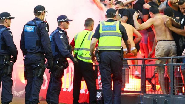 Smoke alarm: Wanderers fans let off flares as police officers look on in Melbourne two weekends ago.