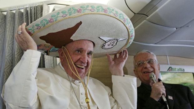 Pope Francis wears a traditional Mexican sombrero hat he received as a gift from a Mexican journalist during the flight ...
