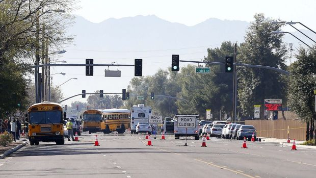 Buses make their way to bring parents waiting to reunite with their children in the Phoenix suburb of Glendale.