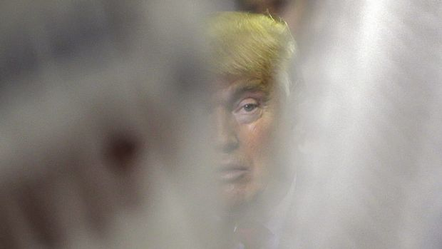 Republican presidential candidate Donald Trump is seen through campaign signs during a rally on Friday.