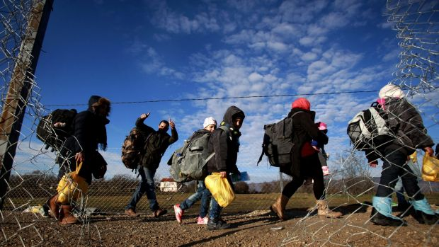 Refugees walk towards the border with Serbia from the transit centre for refugees near the northern Macedonian village ...